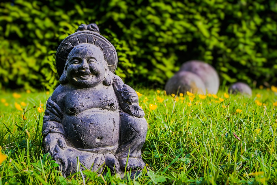laughing buddha statue with yellow flowers in background