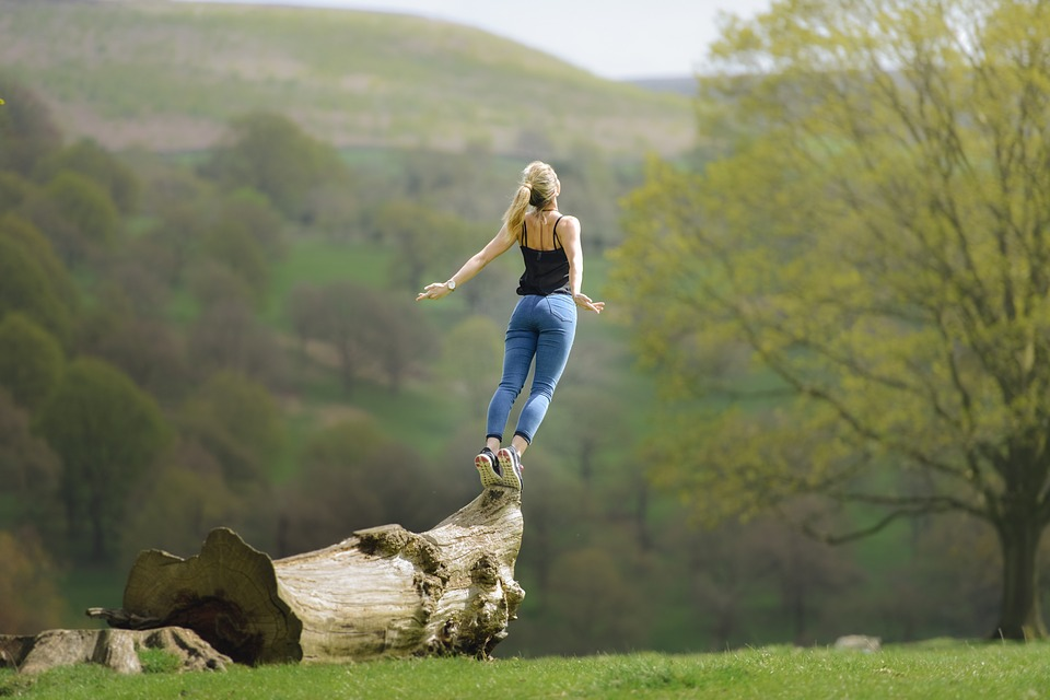 woman on tip toes on top of a fallen tree