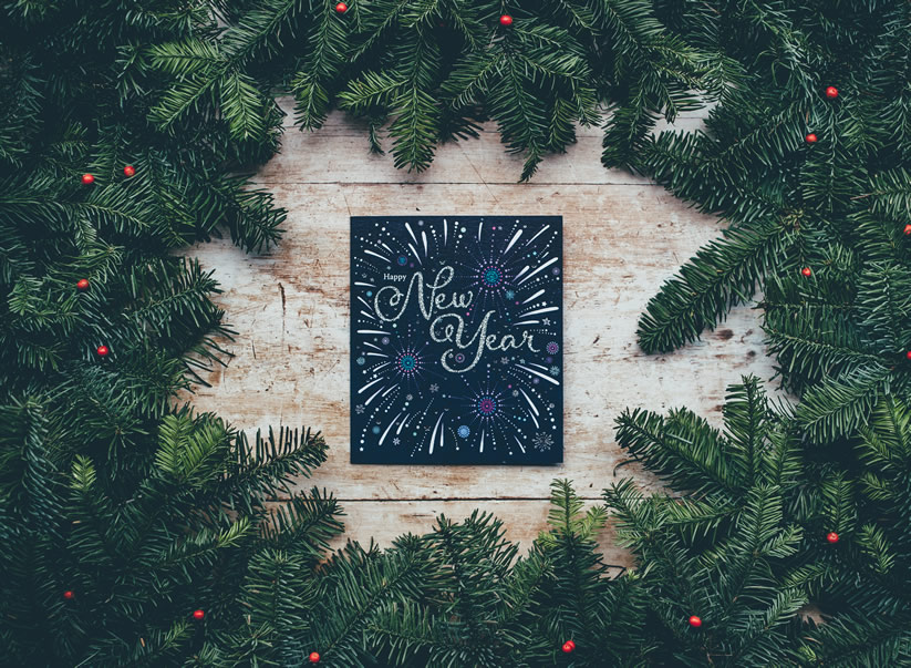 new year card on wooden table surrounded by evergreens