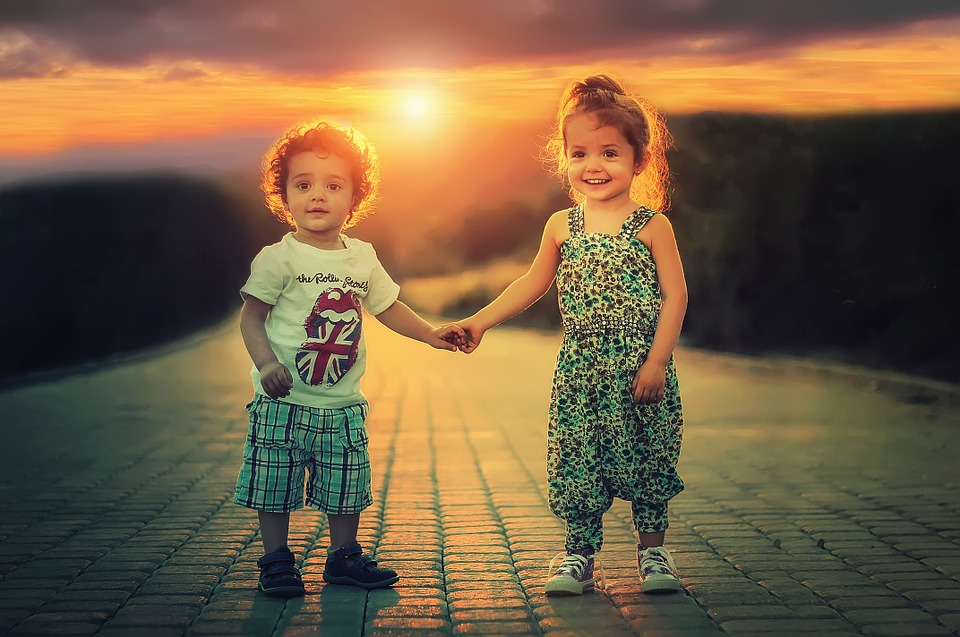 kids holding hands on path with sunset