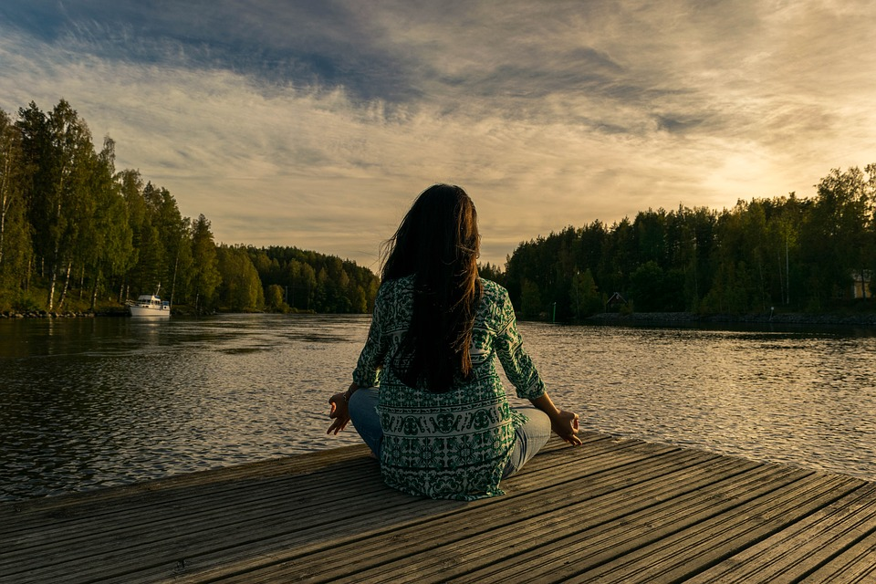 woman sitting on dock in yoga pose